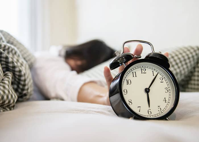 woman overslept reaching for the alarm